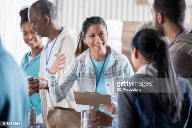 food bank manager organizes group of volunteers - homeless shelter stock pictures, royalty-free photos & images