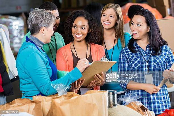 food bank manager talks with volunteers - charity benefit stock pictures, royalty-free photos & images
