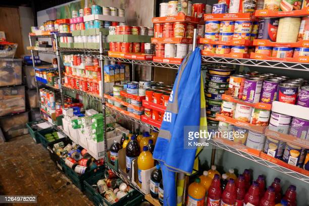 food bank shelving filled with donated tinned food ready for distribution - food bank stock pictures, royalty-free photos & images