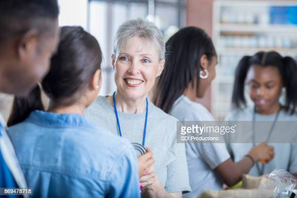 food bank volunteer coordinator talks with volunteers - non profit organization stock pictures, royalty-free photos & images