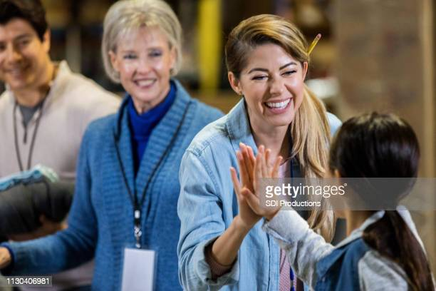 food bank volunteer gives high five to little girl - charity benefit stock pictures, royalty-free photos & images