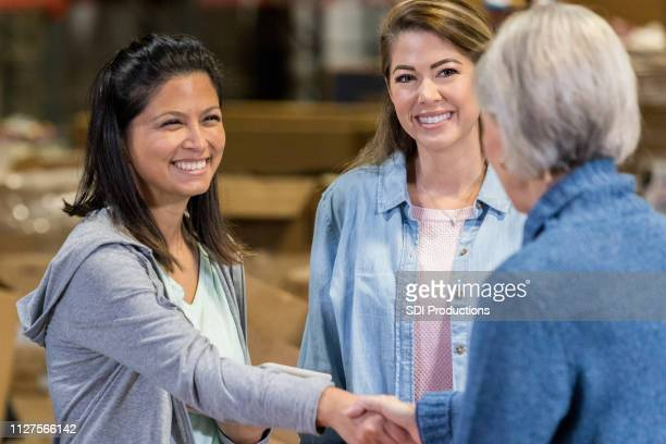 food bank volunteer greets new customer - non profit organization stock pictures, royalty-free photos & images