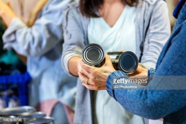 food bank volunteer hands out donated food items - food bank stock pictures, royalty-free photos & images
