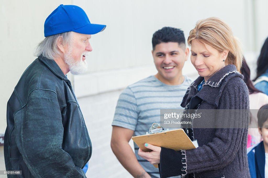 Food bank volunteer helps homeless man : Stock Photo