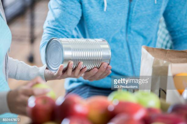 food bank volunteer organize food donations - canned food stock pictures, royalty-free photos & images