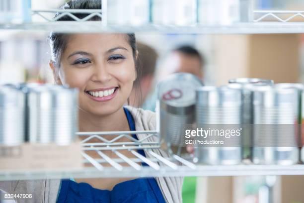 Food bank volunteer stocks shelves in food bank