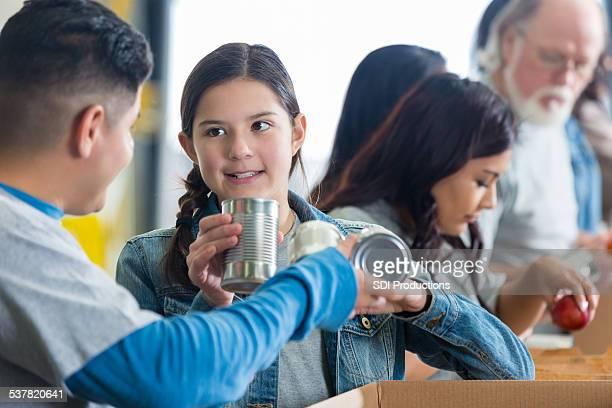 Food bank volunteer teaching preteen to sort donations