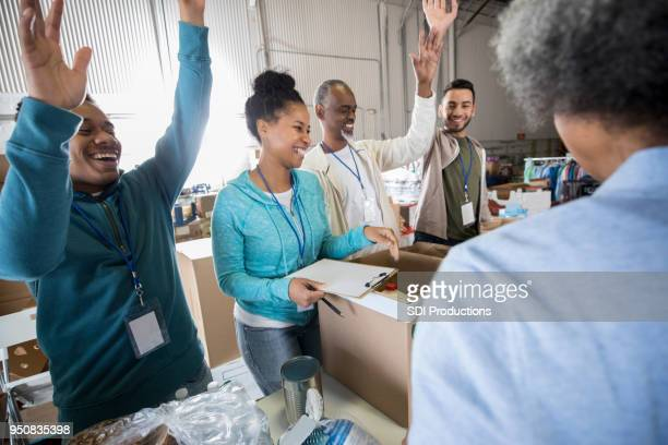 food bank volunteers enjoy joke together - homeless shelter stock pictures, royalty-free photos & images