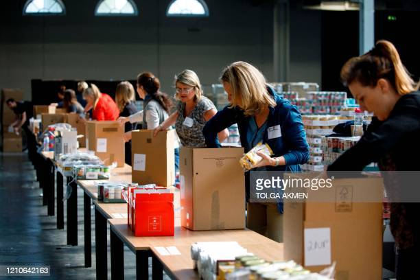 Food bank volunteers pack food into boxes for people in need at a temporary food bank at Kensington Olympia in west London on April 22 as Britain...