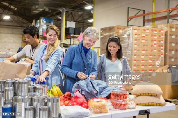 food bank volunteers sort donations - food pantry stock pictures, royalty-free photos & images