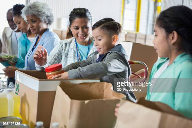 food bank volunteers sort out food donations - homeless shelter stock pictures, royalty-free photos & images