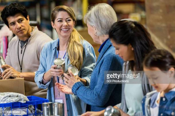 food bank volunteers sort through canned food items - charity benefit stock pictures, royalty-free photos & images
