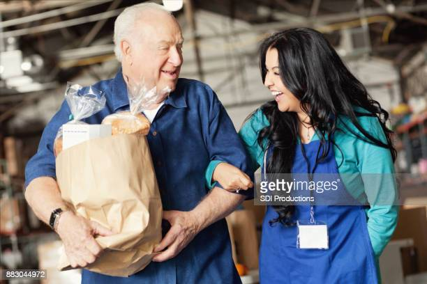 A food bank worker walks arm in arm with a senior patron