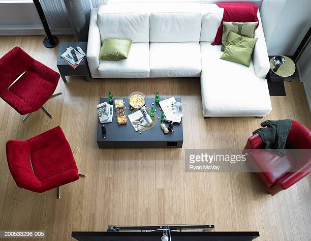 Food, beer and newspaper on coffee table in living room, elevated view