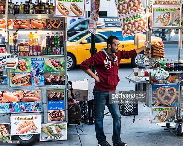CONTENT] A food cart vendor surrounded by carts and adverts for pretzels hot dogs cold drinks kebabs etc