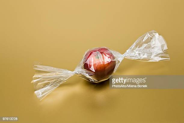 food concept, fresh apple inside cellophane candy wrapper - candy wrapper stock photos and pictures