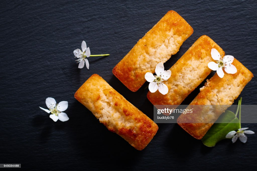 Food concept mini French almond cake financier on black slate stone with copy space : Stock Photo