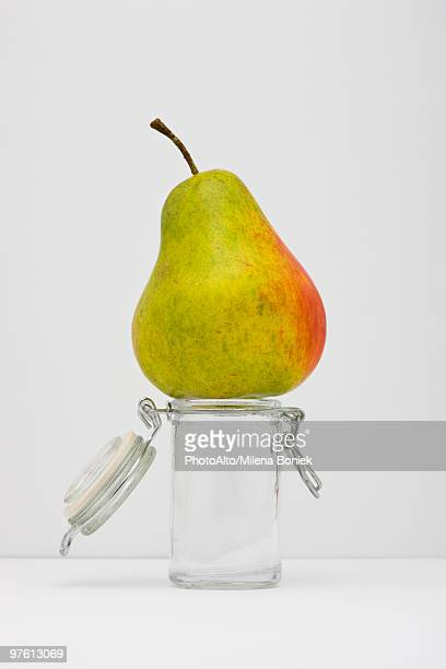 Food concept, pear on top of small glass jar