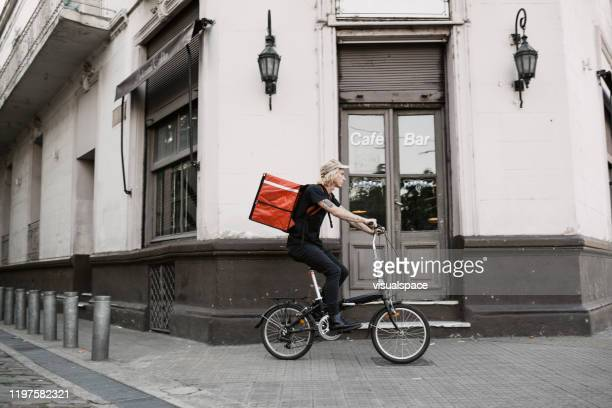 food courier cycling in the city - montare foto e immagini stock