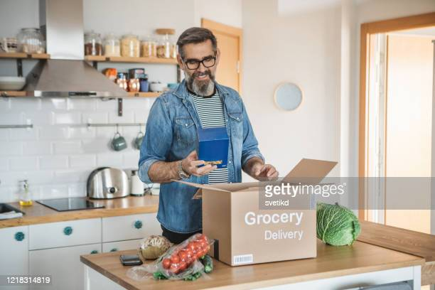food delivering in pandemic situation - unpacking stock pictures, royalty-free photos & images