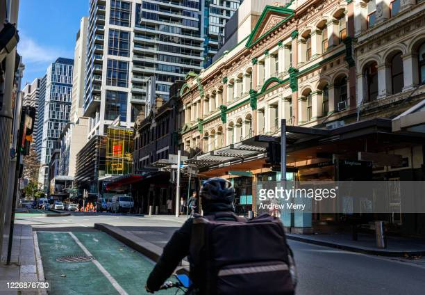 food delivery bike driver cycling in bike lane in sydney city - essential workers stock pictures, royalty-free photos & images