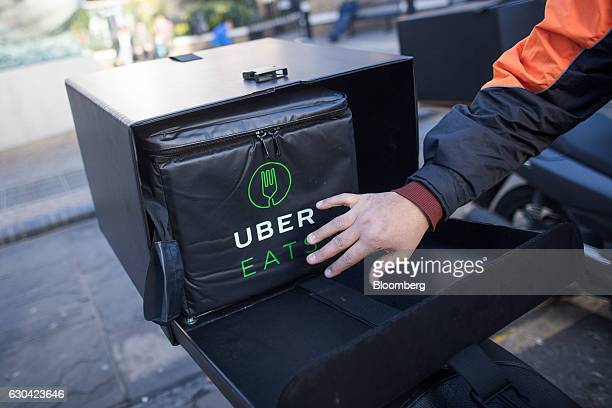 A food delivery courier puts an insulated food bag in his UberEats operated by Uber Technologies Inc branded box on his motor scooter in London UK on...