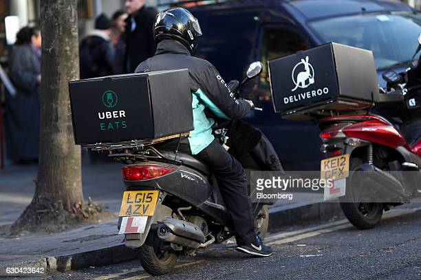 A food delivery courier wearing a Deliveroo operated by Roofoods Ltd branded jacket sits on a motor scooter with an UberEats operated by Uber...