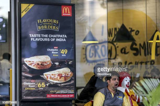 A food delivery courier yawns while sitting next to a statue of Ronald McDonald as menu items are displayed in the window of a McDonald's Corp...
