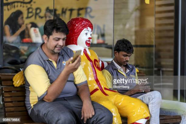 Food delivery couriers look at smartphones while sitting next to a statue of Ronald McDonald outside a McDonald's Corp restaurant operated by...