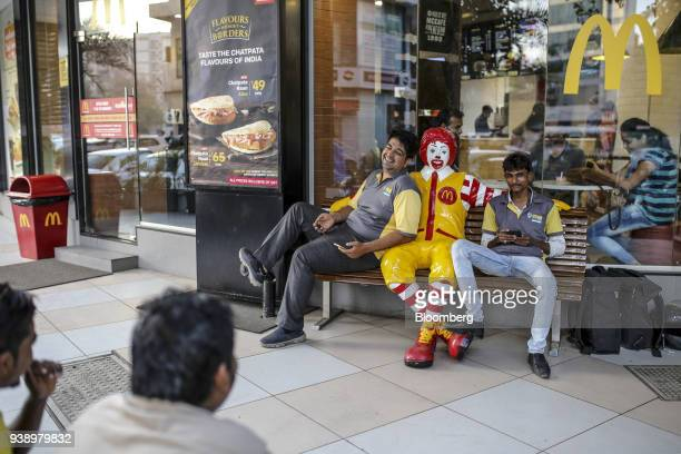 Food delivery couriers sit next to a statue of Ronald McDonald outside a McDonald's Corp restaurant operated by Hardcastle Restaurants Pvt in Mumbai...