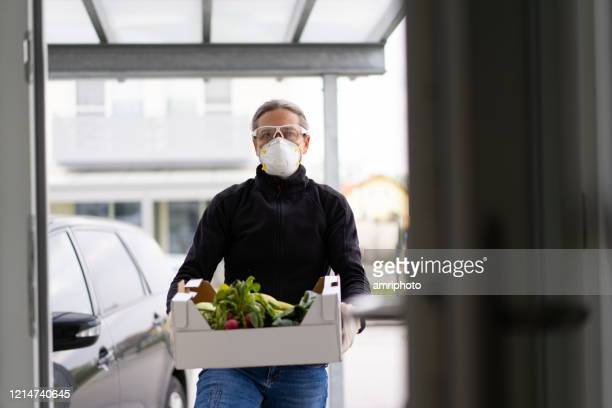 food delivery during covid-19 - delivery person stock pictures, royalty-free photos & images