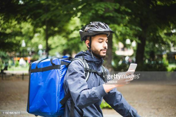 Food delivery man using smart phone on street in city