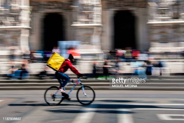Food delivery rider cycles across Duomo square in Milan on March 25, 2019.