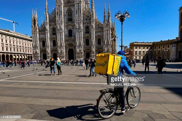 Food delivery rider cycles by the cathedral across Duomo square in Milan on March 25, 2019.
