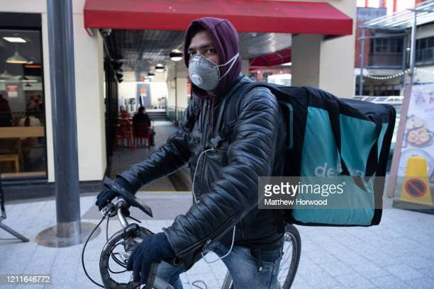 Food delivery rider poses for a photograph while wearing a N95 respirator on March 8, 2020 in Cardiff, United Kingdom. Food delivery services have...