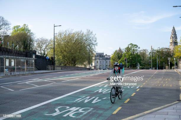 A food delivery rider wears a surgical face mask while riding a bike on April 19 2020 in Cardiff United Kingdom The Coronavirus pandemic has spread...