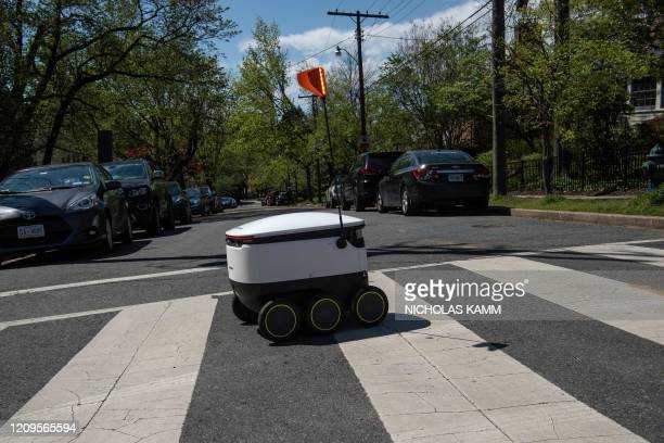 A food delivery robot from the Broad Branch Market grocery store crosses a street in the Chevy Chase neighborhood of Washington DC on April 9 2020 on...