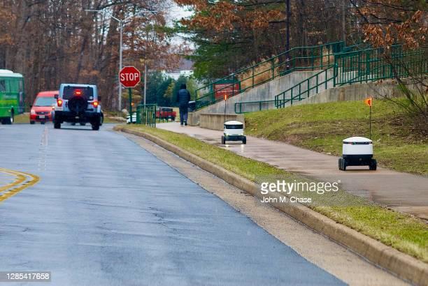 les robots de livraison de nourriture voyagent les uns vers les autres - véhicule terrestre sans pilote photos et images de collection