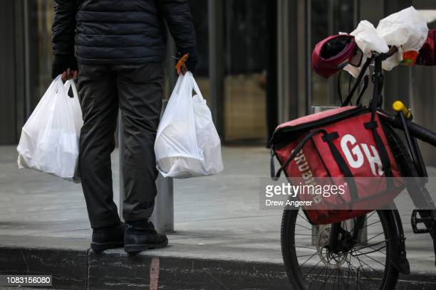 A food delivery worker carries a plastic bags in Lower Manhattan January 15 2019 in New York City New York Governor Andrew Cuomo is planning to push...