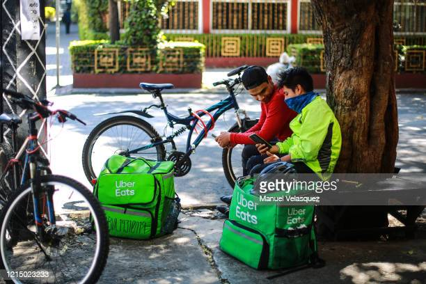 Food delivery workers await for services at Condesa neighborhood during the global crisi of coronavirus pandemic on March 26 2020 in Mexico City...
