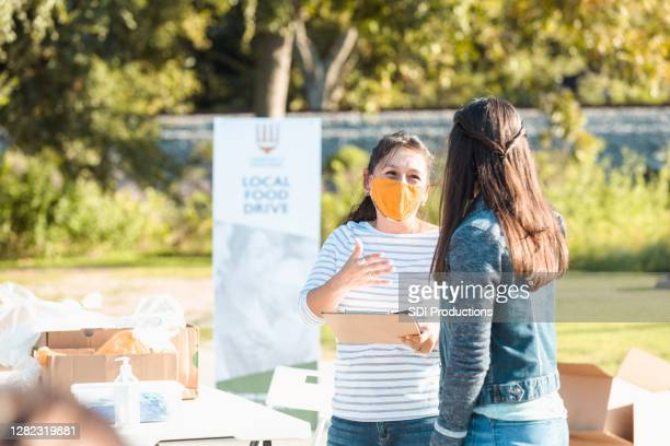 food drive coordinator wears protective mask during covid-19 - giving tuesday stock pictures, royalty-free photos & images