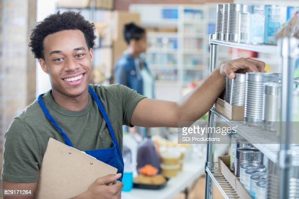 food drive director organizes canned food - food bank stock pictures, royalty-free photos & images
