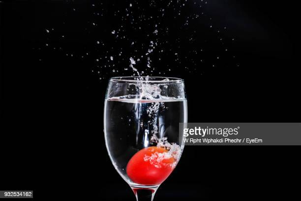 Food Falling In Wineglass With Splashing Water Against Black Background