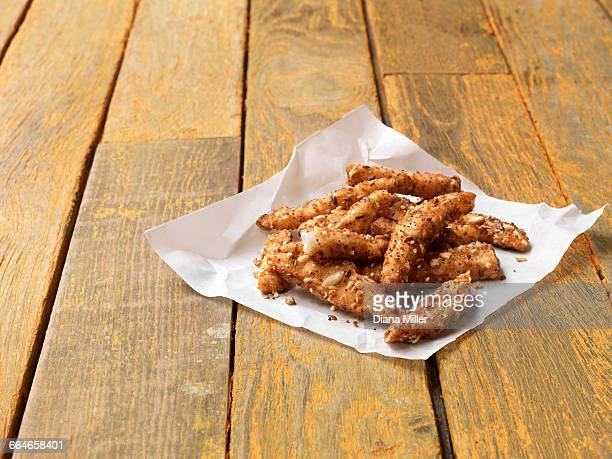 Food, fish, super seeded lightly dusted plaice goujons, painted yellow wooden table