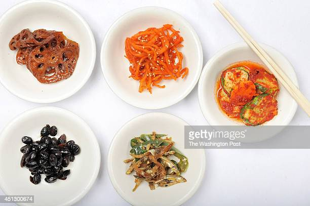 Food from top row lotus root sliced squid cucumbers and bottom row braised beans and anchovies are seen at Nak Won Restaurant on Wednesday June 04...