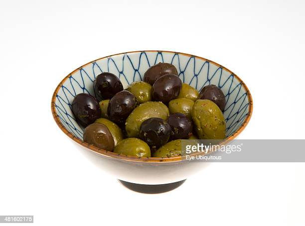 Food Fruit Olives Ripe black and green olives Olea europaea in olive oil in a bowl against a white background