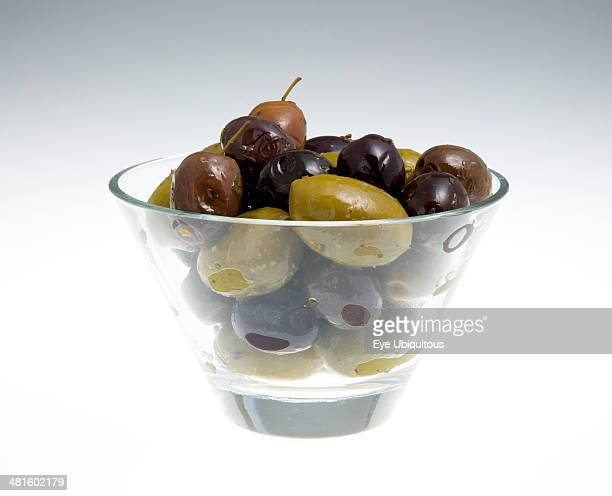 Food Fruit Olives Ripe black and green olives Olea europaea in olive oil in a glass bowl against a white background