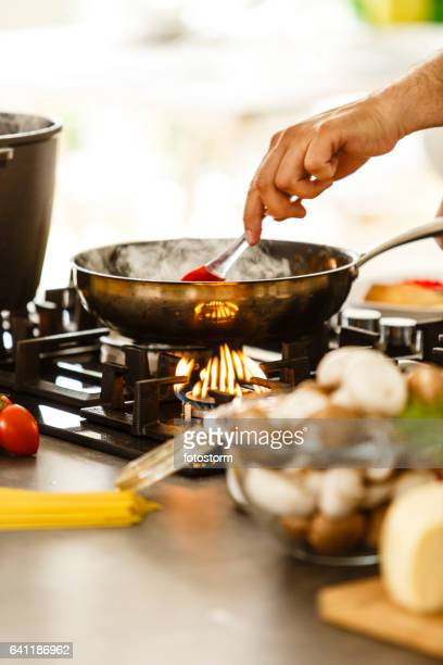 Food in a frying pan being stirred with a spoon