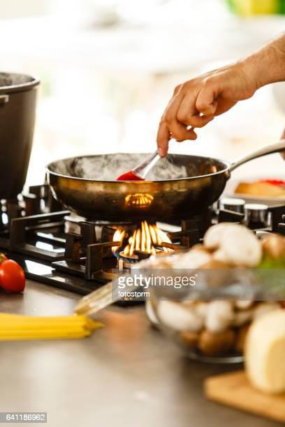Eten in een koekenpan wordt geroerd met een lepel