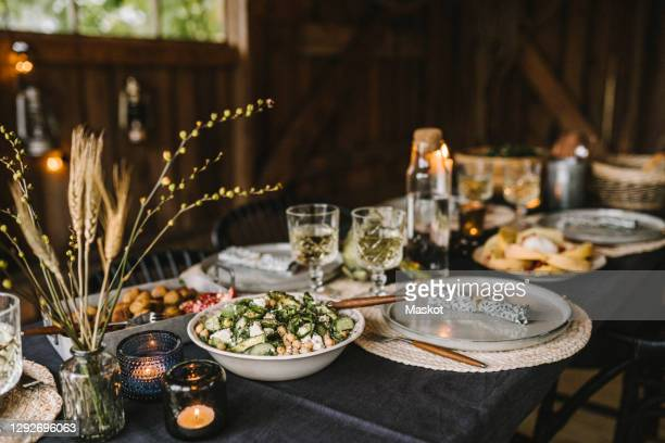 food in bowl by plate and drinking glass arranged on dining table during social gathering - candle stock pictures, royalty-free photos & images